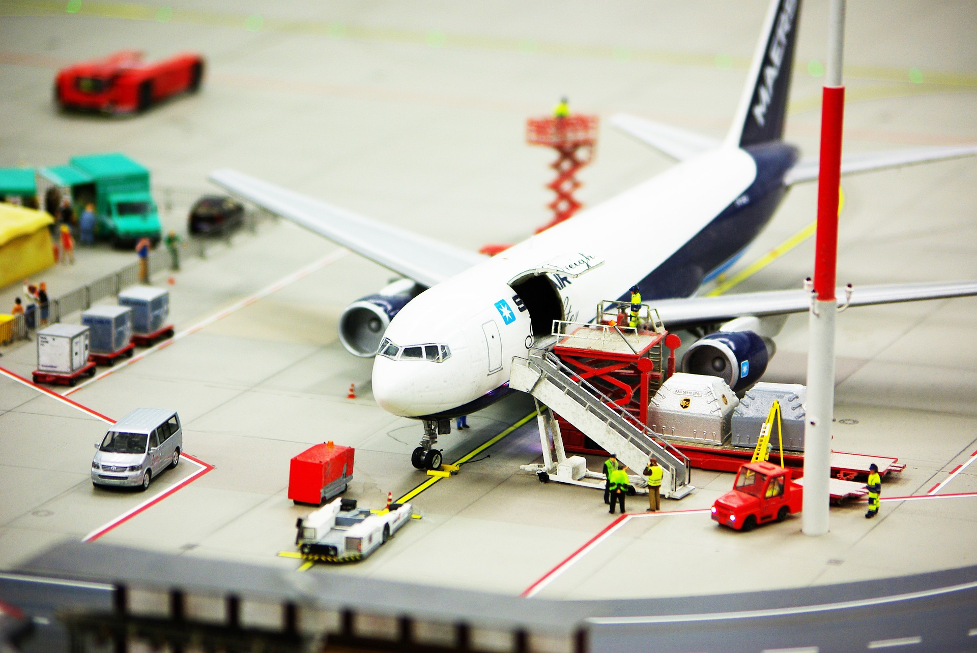 A bird's eye view of a scissor lift pallet truck in action in an airport.